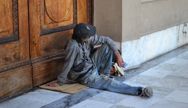 Beggar sitting at doorstep