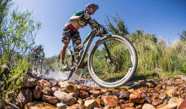 Cape Epic bikers ride through a streem