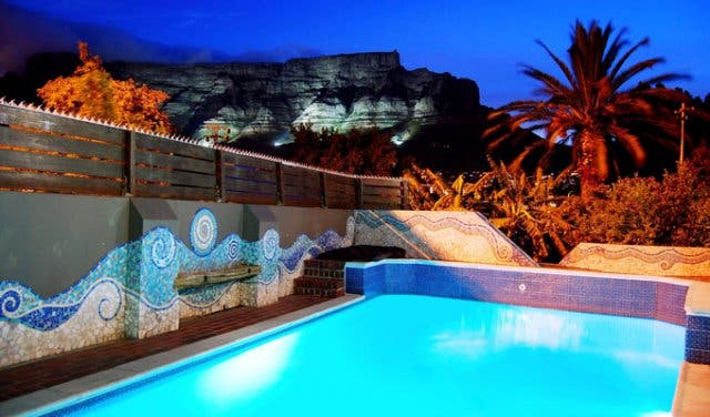 Swimming pool at night with Table Mountain in the background